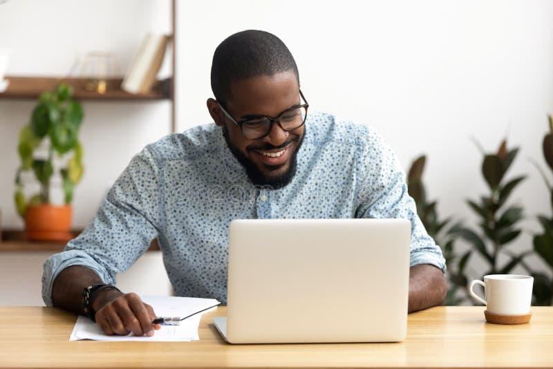 La testa ha sparato al responsabile afroamericano sorridente facendo uso del computer portatile che esamina lo schermo immagini stock