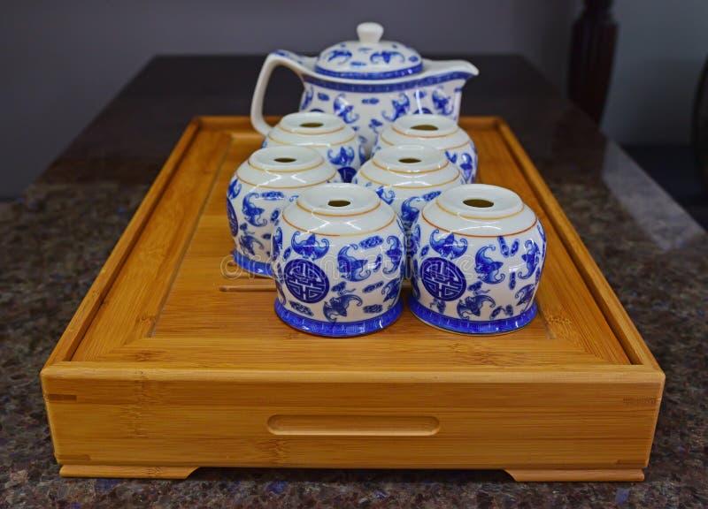 La tetera azul china de la porcelana fijó en la bandeja de madera tradicional imagen de archivo libre de regalías