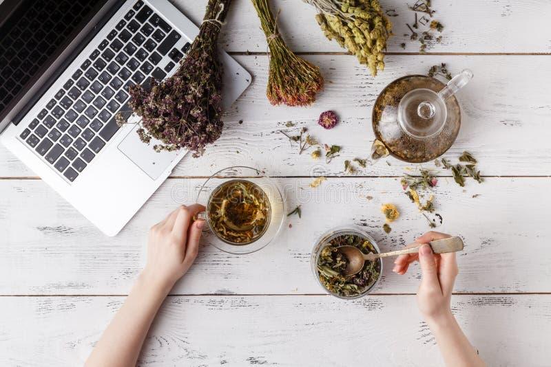 La tetera con infusión de hierbas en la tabla de cocina y la mujer escriben receta fotos de archivo