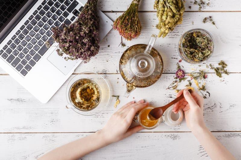 La tetera con infusión de hierbas en la tabla de cocina y la mujer escriben receta imagen de archivo