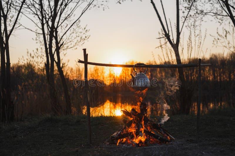 La tetera en el fuego prepara t? Puesta del sol anaranjada imagen de archivo libre de regalías