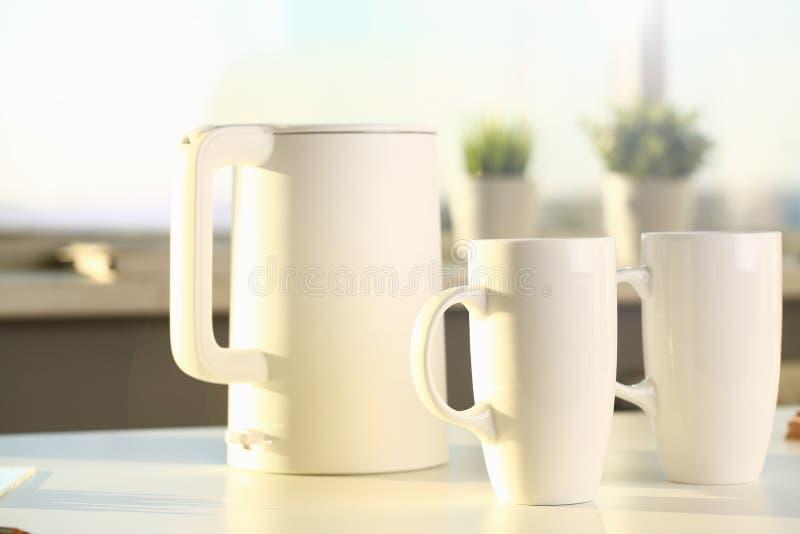 La tetera y dos tazas de moda est?n en la tabla para imagenes de archivo