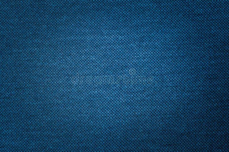 La textura azul marino de la tela del paño que es estructural fondo de las fibras de la tela de materia textil nos utiliza espaci fotografía de archivo