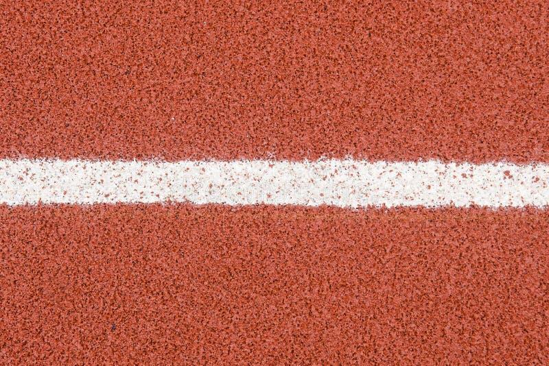 La textura de goma de la cubierta de los carriles de la pista corriente con la línea para el fondo imágenes de archivo libres de regalías