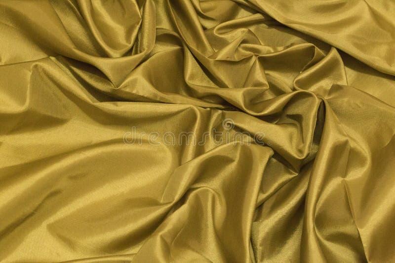 La textura de lujo elegante lisa del paño de la seda o del satén del oro puede utilizar a fotografía de archivo libre de regalías