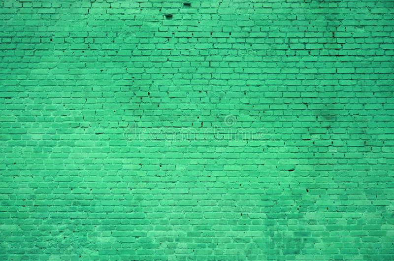 La textura de la pared de ladrillo de muchas filas de los ladrillos pintados en colo verde imagenes de archivo