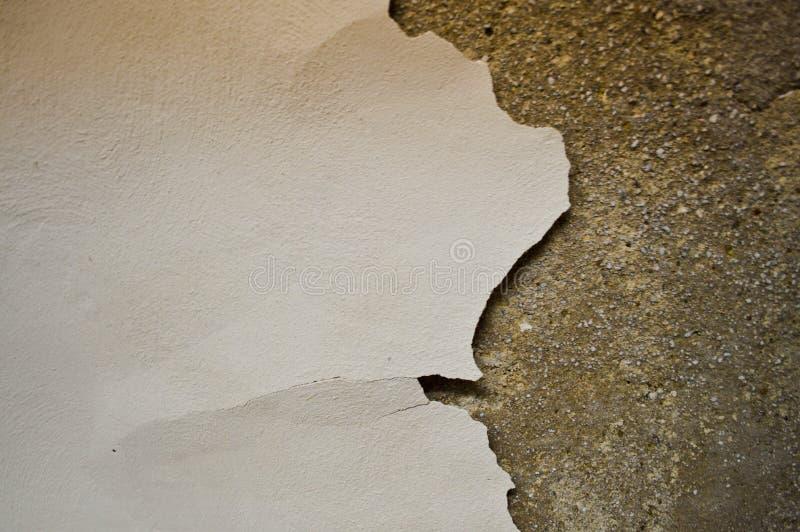 La textura de la pared lamentable vieja concreta de la piedra con las grietas y microprocesadores que blanquean y yeso exfoliated imagen de archivo