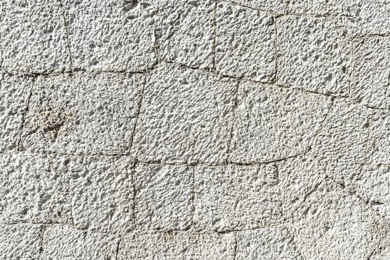 La textura de la pared de piedra blanca vieja con las grietas se cierra para arriba foto de archivo