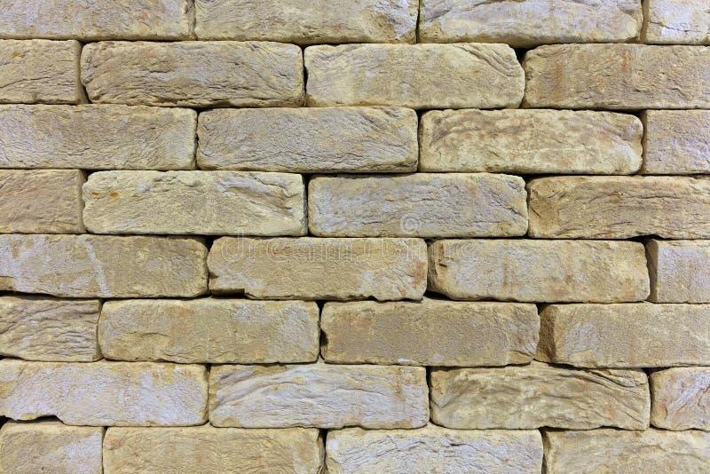 La textura de la pared de piedra del ladrillo viejo, piedra de construcción de la piedra arenisca beige-de oro foto de archivo