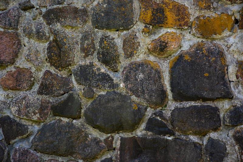 La textura de la pared de piedra vieja de los guijarros grandes demasiado grandes para su edad con el musgo imágenes de archivo libres de regalías