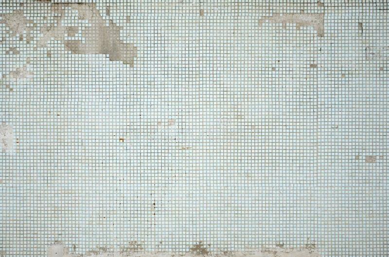 La textura de la pared vieja, adornada con muchas pequeñas tejas cuadradas Pared en el estilo de la arquitectura de la Unión Sovi foto de archivo libre de regalías