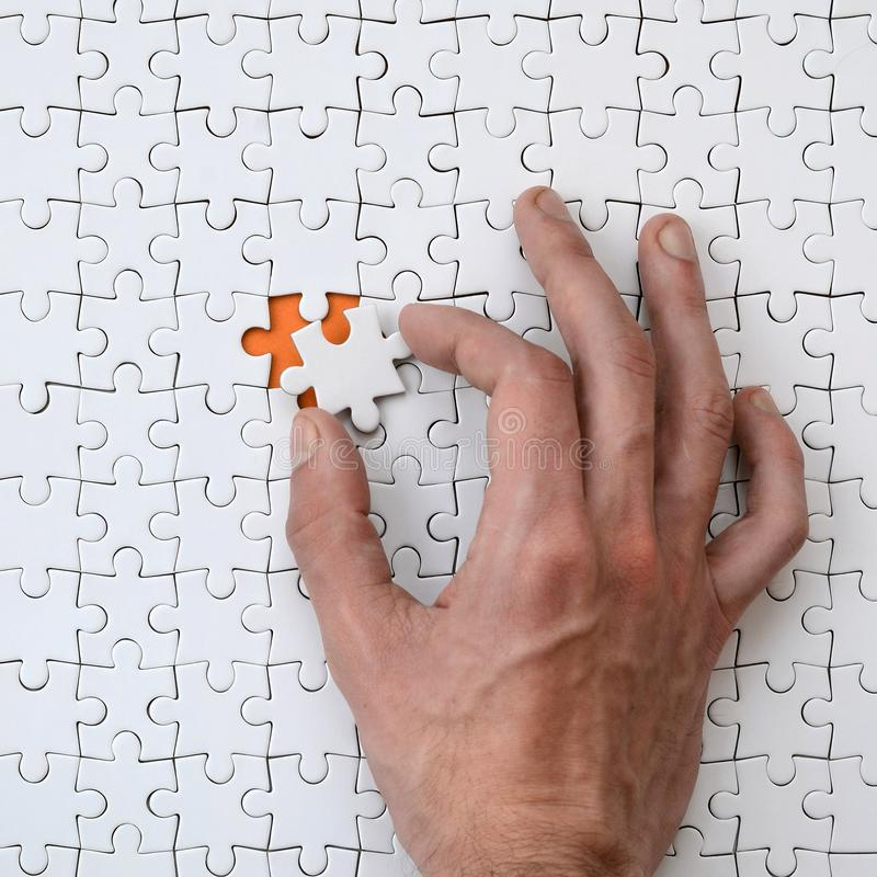 La textura de un rompecabezas blanco en el estado montado con un elemento perdido que la mano masculina introduce fotografía de archivo libre de regalías