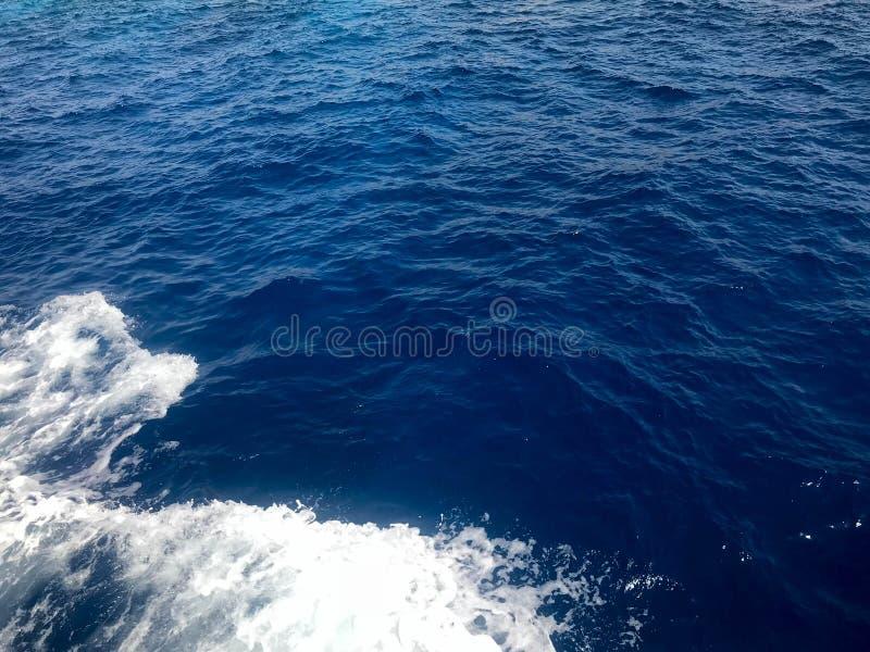 La textura de una agua de mar mojada azul que burbujea con las ondas, burbujas, espuma blanca, salpica, salpica, cae Los antecede fotos de archivo
