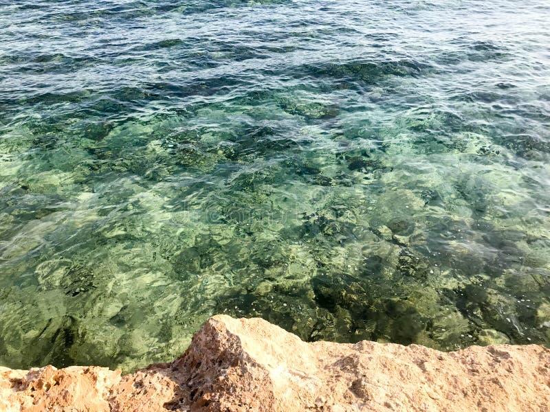 La textura de una playa arenosa de piedra hermosa, de una tierra, de una playa y de un agua azul verdosa, el mar en un balneario  imagen de archivo libre de regalías