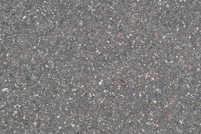 La textura del fondo de la carretera de asfalto gris del negro de la piedra con los pequeños guijarros imagenes de archivo