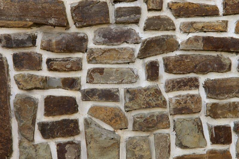 La textura del fondo de la pared se hace de la piedra marrón natural de diversas formas con el cemento blanco foto de archivo libre de regalías