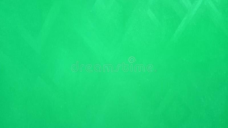 La textura lisa de los tri?ngulos del papel verde claro abstracto reflej? en el papel pintado del fondo del papel fotografía de archivo