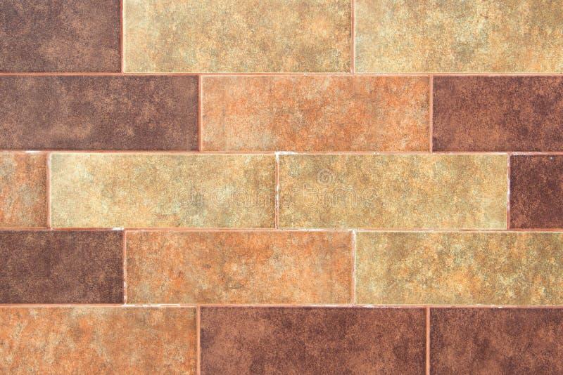 La texture d'un mur de briques des briques rectangulaires multicolores décoratives avec le bruit, éraflures photographie stock