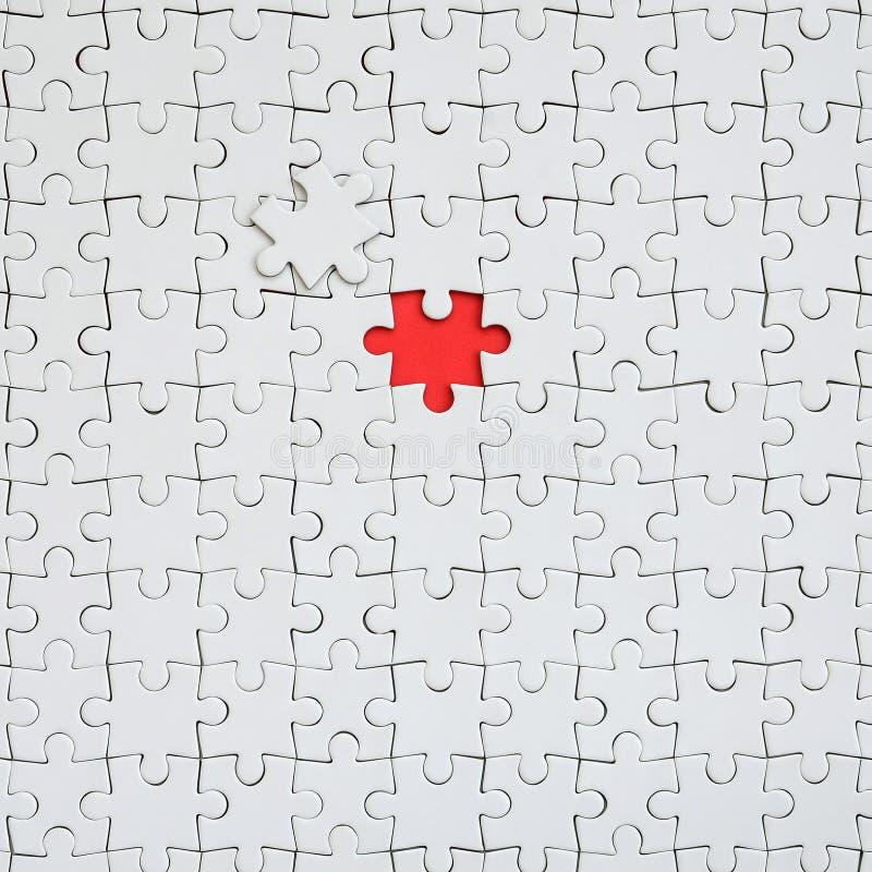 La texture d'un puzzle denteux blanc dans un état assemblé avec un élément absent formant un espace rouge photos libres de droits
