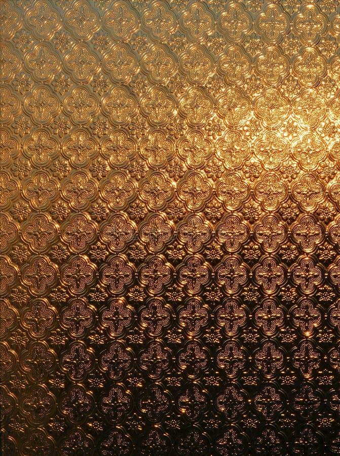 La texture d'un vitrail givré par lequel le Soleil Levant brille a une couleur d'or-brune images libres de droits