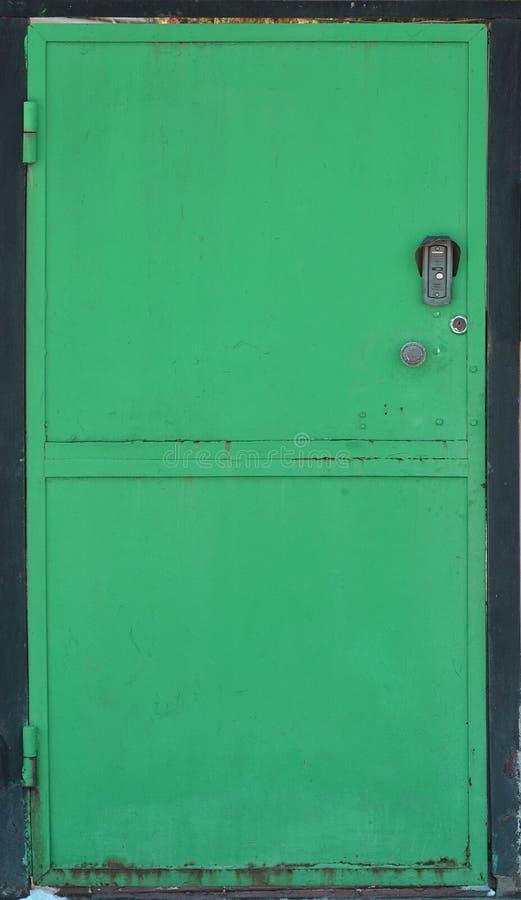 La texture d'une porte peinte en métal d'un mur de briques images stock