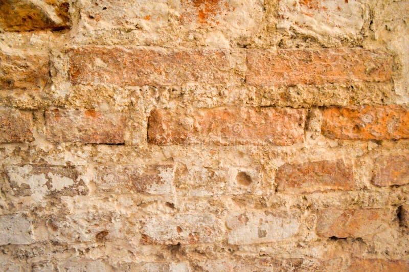 La texture de la vieille pierre vigoureuse antique médiévale antique épluchant le mur rayé de la brique lumineuse orange rouge re image libre de droits