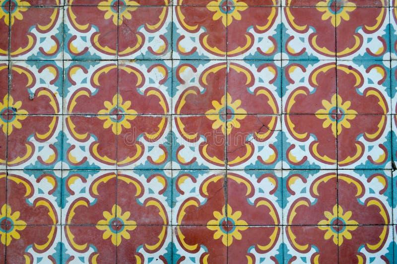 La texture des carreaux de céramique carrés avec des modèles des ornements et des fleurs arabes traditionnels de jaune et de bleu photo stock