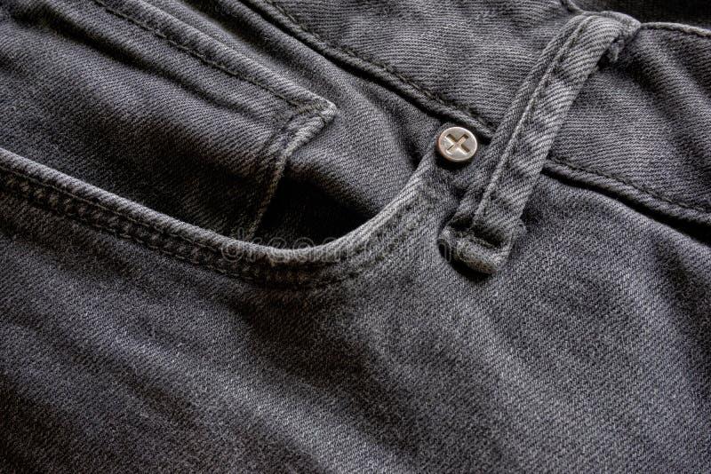 La texture des jeans noirs avec la poche et la ceinture font une boucle images stock