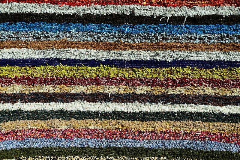 La texture du tapis fait main pelucheux a produit sur le main-métier à tisser, modèle de diverses lignes verticales colorées photos libres de droits