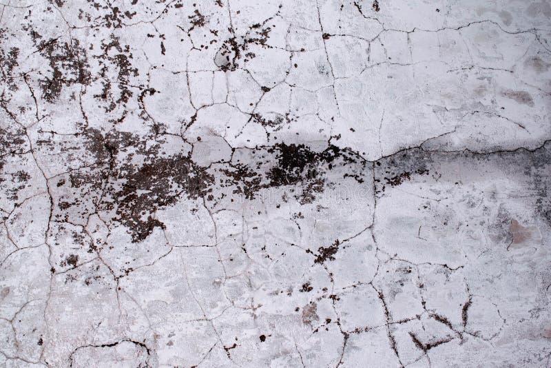 La texture du vieux mur en béton est couverte de fissures et de taches de moule, fond minable Papier peint grunge de style photo libre de droits