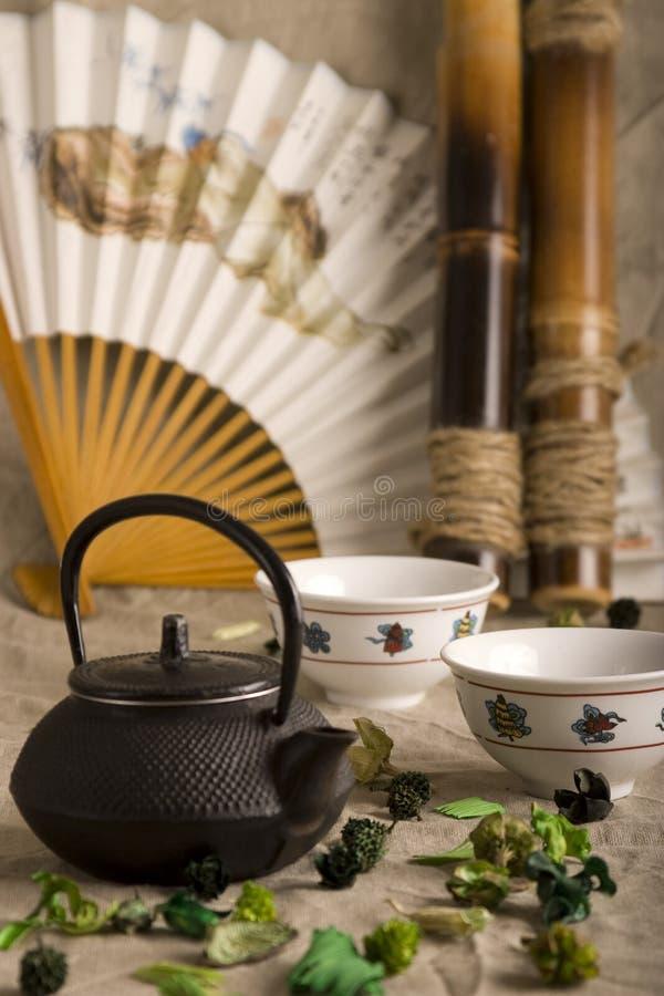 La théière chinoise, deux cuvettes, ventilateur et bambou images libres de droits