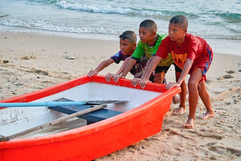 La THAÏLANDE PHUKET le 18 mars 2018 - trois enfants poussant un bateau de pêche au rivage Concept du travail des enfants de l'abo image stock