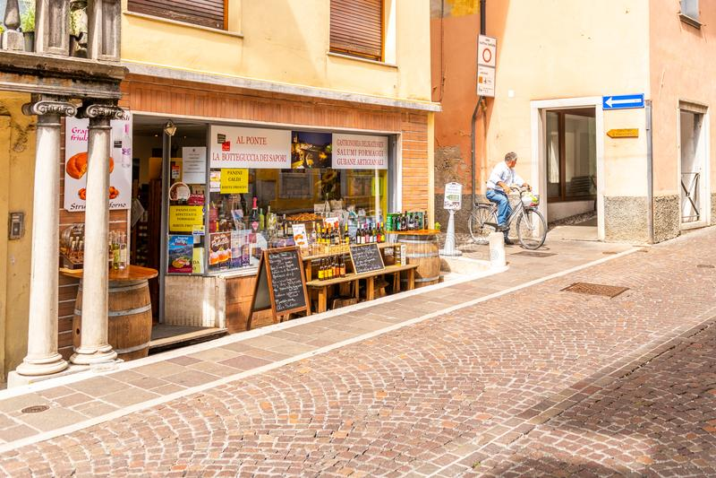 La tienda de delicatessen turística de la calle hace compras con los productos italianos tradicionales en Cividale del Friuli, It imagen de archivo