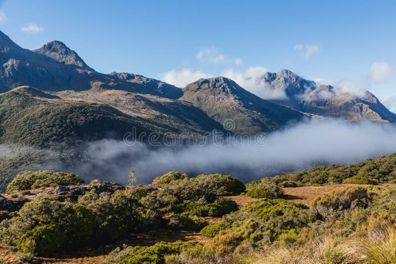 La tierra de la montaña se nubla, el rastro dominante de la cumbre, pista de Routeburn, Nueva Zelanda imagenes de archivo