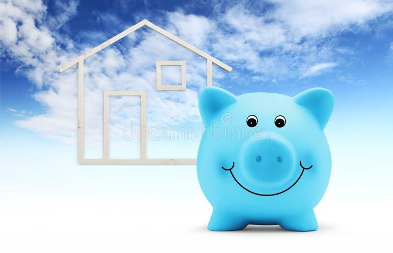 La tirelire avec la forme de maison en bois d'isolement sur le fond de ciel bleu, le bâtiment vert et l'énergie sauvent le concep photos stock
