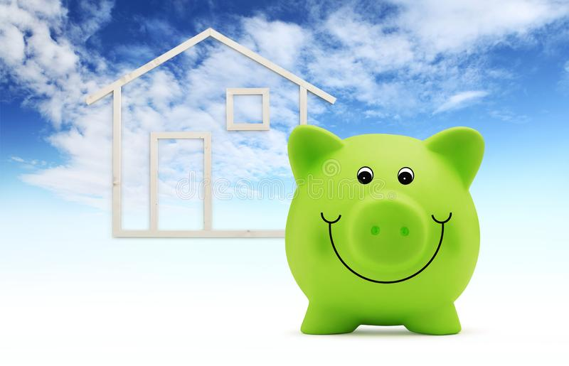 La tirelire avec la forme de maison en bois d'isolement sur le fond de ciel bleu, le bâtiment vert et l'énergie sauvent le concep photo libre de droits