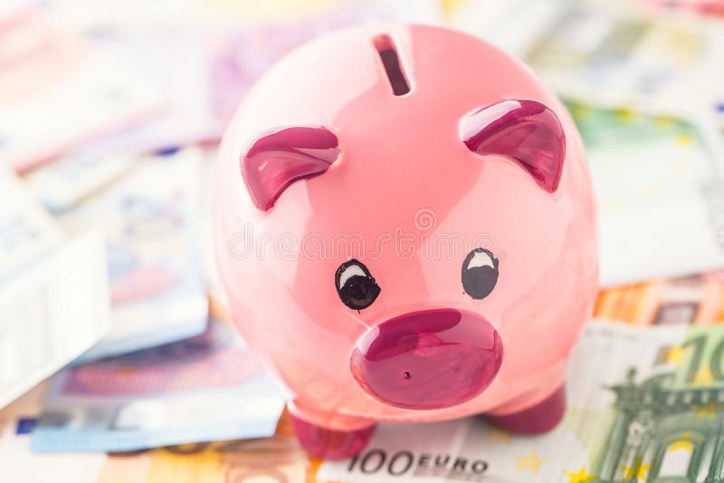 La tirelire se tient sur une grande quantité d'euro billets de banque image stock