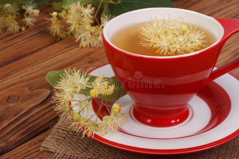 La tisana con il tiglio fiorisce su una tavola di legno marrone fotografia stock