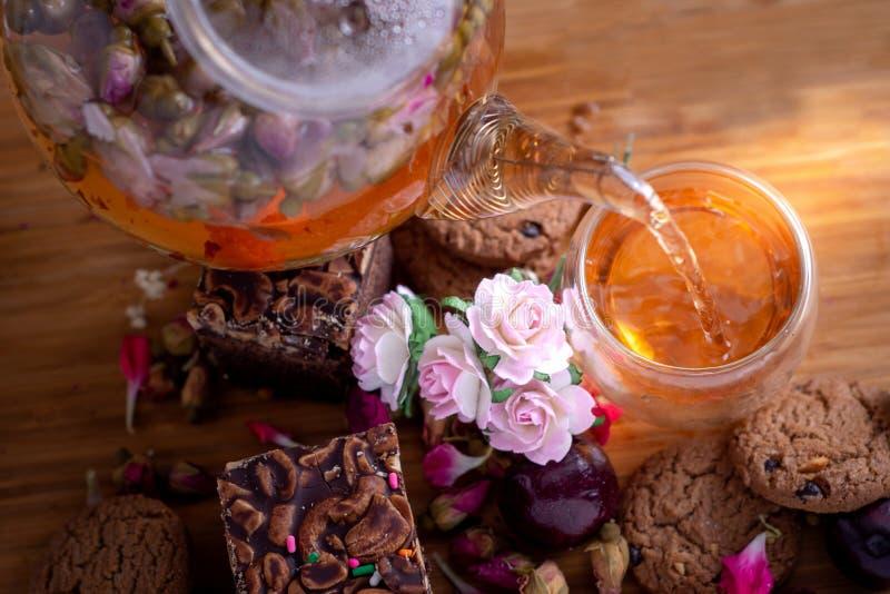 La tisana di versamento dalla teiera nella tazza di tè di vetro con la pila del brownie agglutina immagini stock