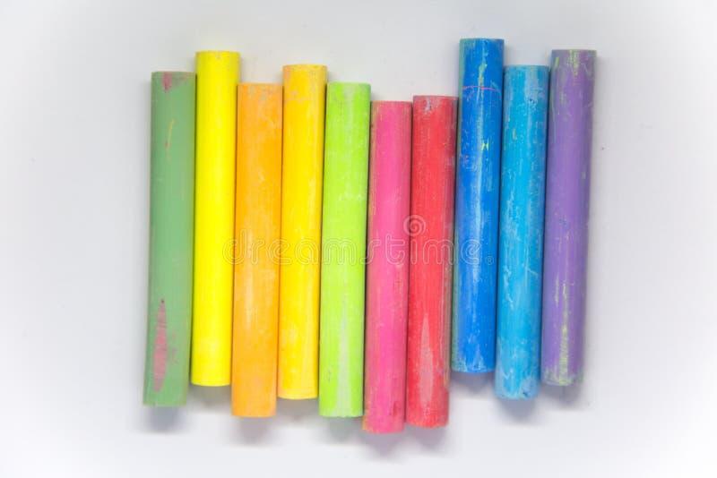 La tiza colorida viva se pega en un Libro Blanco Fuentes de escuela hermosas imagenes de archivo