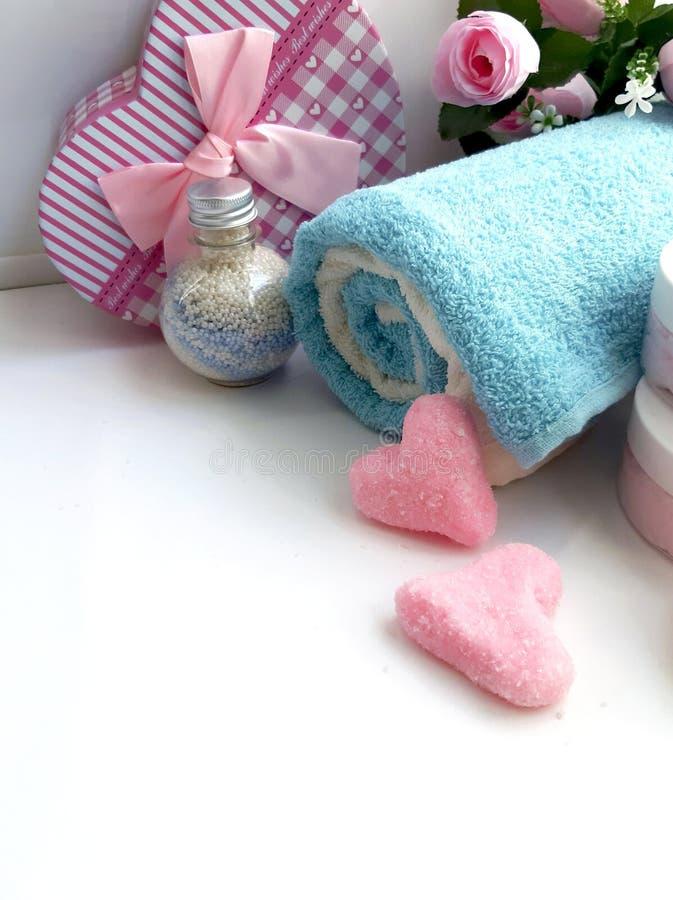 La toalla, caja de regalo, botella cosmética, sal friega la forma del corazón en el fondo blanco imágenes de archivo libres de regalías