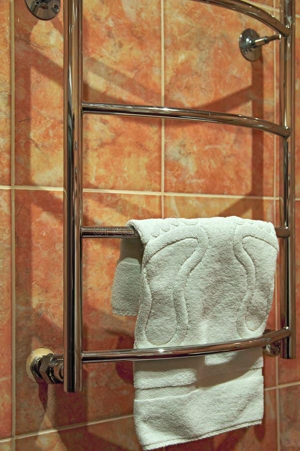 La toalla de Terry blanca cuelga en el cuarto de baño en el carril de toalla heated fotos de archivo libres de regalías