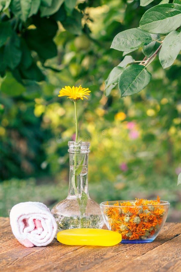 La toalla, jabón con el extracto de la maravilla, calendula florece en un frasco fotos de archivo libres de regalías