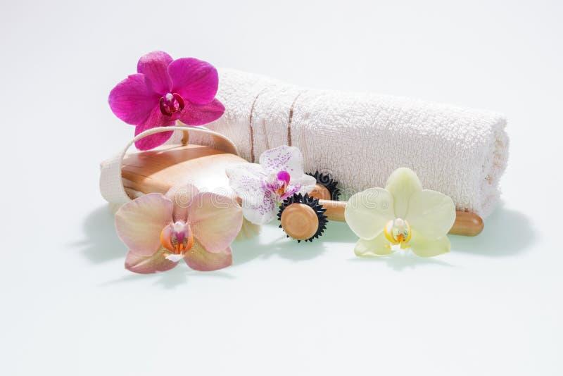 La toalla y el equipo de mano del concepto del balneario con la orquídea florece foto de archivo