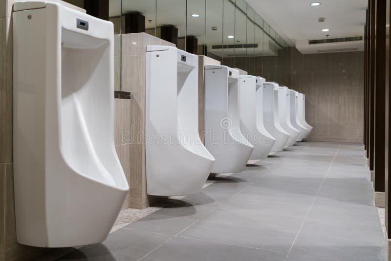 La toilette de l'homme avec la rangée des urinoirs en céramique blancs modernes dans la toilette publique ou le restaurant ou l'h images libres de droits