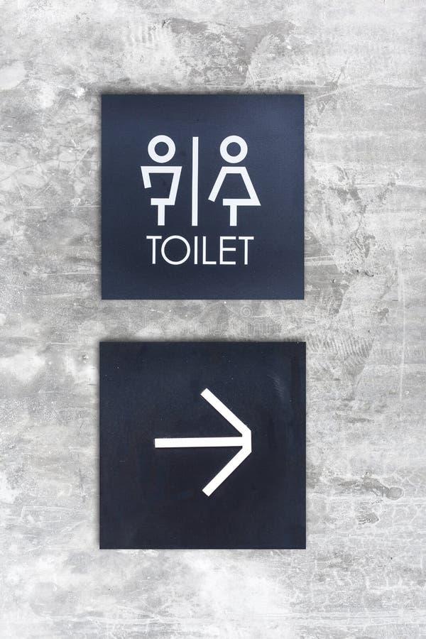 La toilette o la toilette e la freccia unisex firmano su stile del muro di cemento fotografia stock libera da diritti