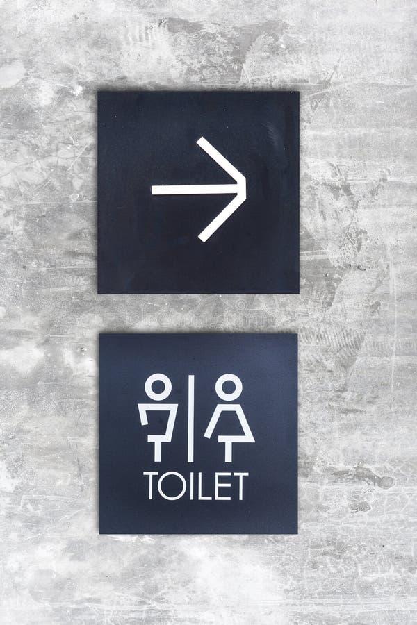 La toilette o la toilette e la freccia unisex firmano su stile del muro di cemento immagini stock libere da diritti