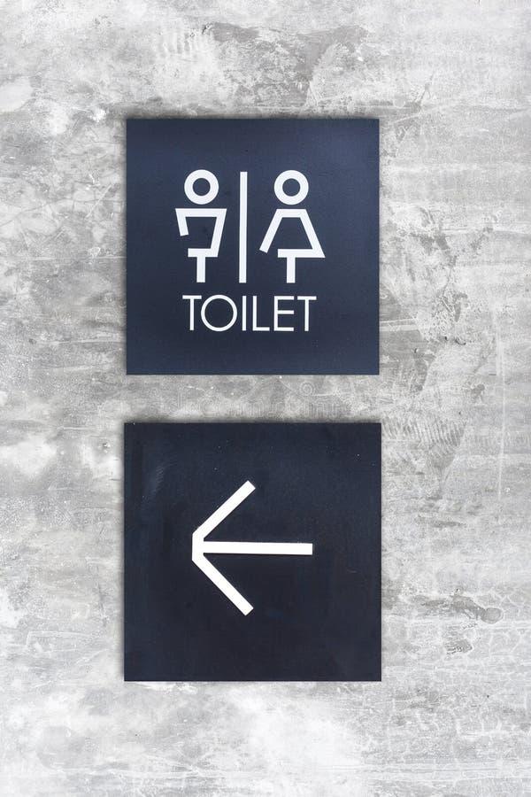 La toilette o la toilette e la freccia unisex firmano su stile del muro di cemento fotografie stock libere da diritti