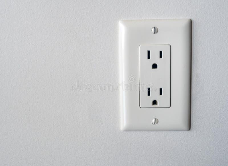 La toma de corriente norteamericana aislada tapa en zócalo en un tipo blanco estilo del fondo de la pared de B imagen de archivo libre de regalías