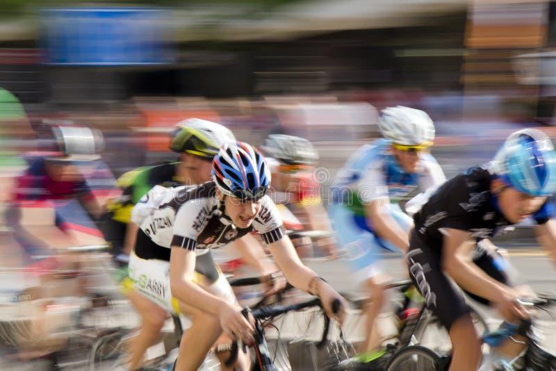 La toma panorámica de la falta de definición de movimiento tiró de la competición joven de los corredores de la bicicleta imagenes de archivo